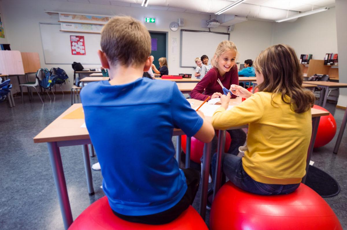 barn i klasserom som smiler