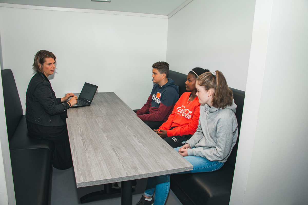 Tre elever blir intervjuet av lærer over et bord